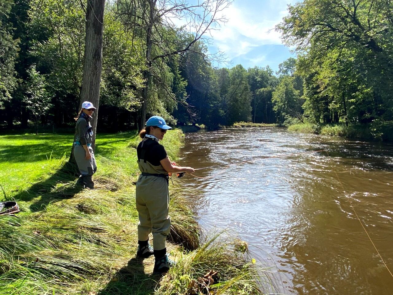 Participants in Casting For Recovery fish along the riverbank