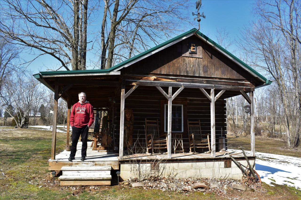 Charles Edwards stands outside a guest cabin located on the 25-acre homestead where he lives in Bedford, Indiana.