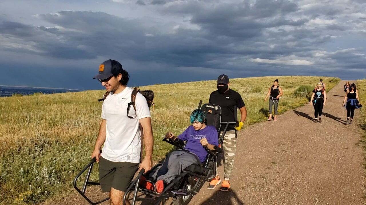 Volunteers with The Lockwood Foundation help a TrailRider wheelchair user access a trail.