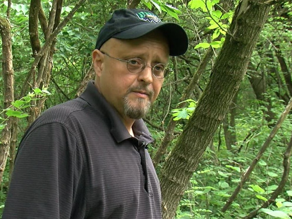 Michael Morgan is pictured here standing in the overgrown Potter's Field cemetery. He is wearing a black Ohio University baseball cap and a black shirt.