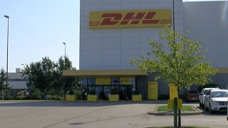 DHL Express hub at the Cincinnati/Northern Kentucky International Airport. The large building has white panels and a yellow and red DHL sign.
