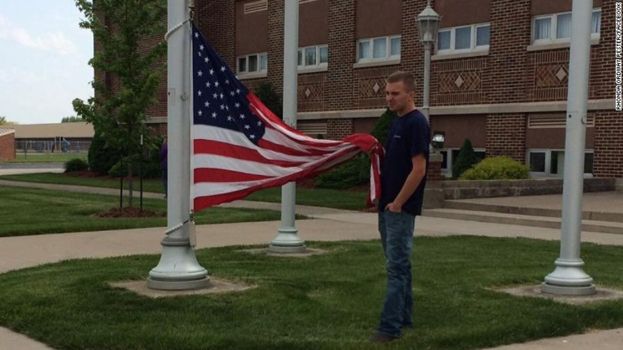 Teen keeps American flag from hitting the ground
