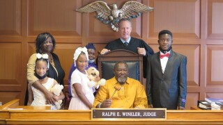 Hamilton County Judge Ralph Winkler, standing behind his chair, poses for a photo with Karen and Tobias Thompson and the four children the Thompsons adopted Thursday.