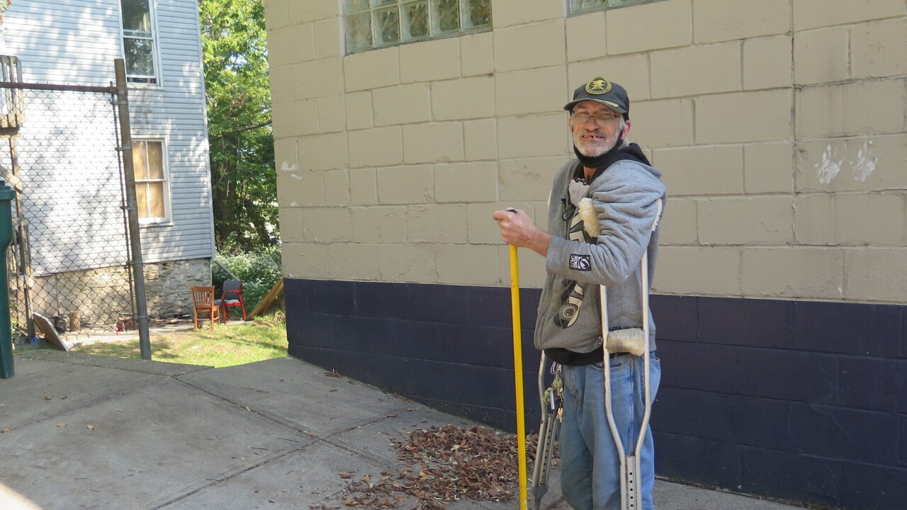 Terry Walls poses with a broom outside the Joe Williams Family Center in Lower Price Hill. He is a paraplegic and uses crutches to walk.