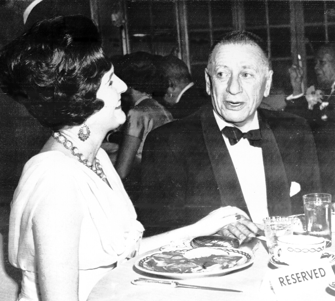 """Pamela Churchill, former daughter-in-law of Sir Winston Churchill, and Mr Leland Hayward, a Broadway showman, at a party given for the opening of the Broadway musical """"The Sound of Music."""""""