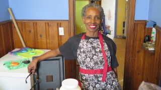 Miranda Heard is standing in her home and smiling in this photo. She has short black and grey hair and is wearing a black t-shirt and a black and white patterned apron with red trim. She's holding glasses in her right hand.