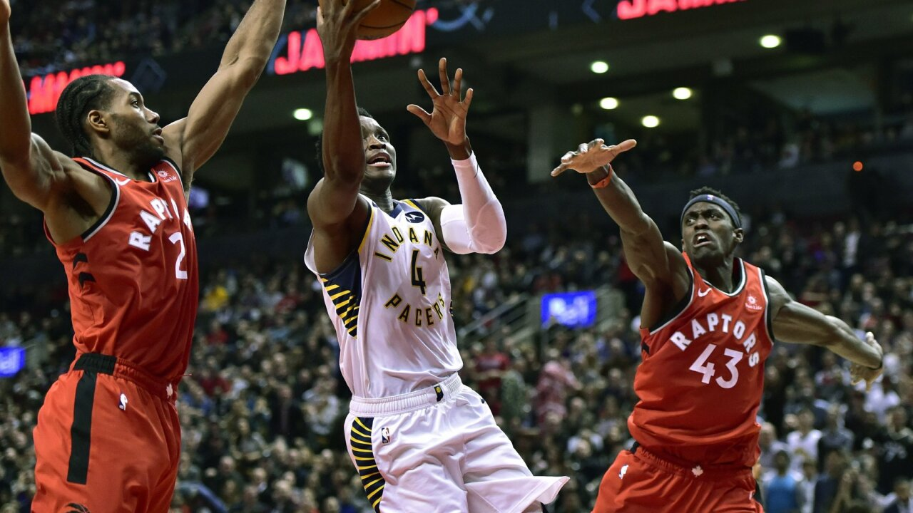 Indiana Pacers guard Victor Oladipo (4) drives to the basket between Toronto Raptors forward Kawhi Leonard (2) and Toronto Raptors forward Pascal Siakam (43) during the second half of an NBA basketball game, Wednesday, Dec. 19, 2018 in Toronto. (Frank Gunn/The Canadian Press via AP)