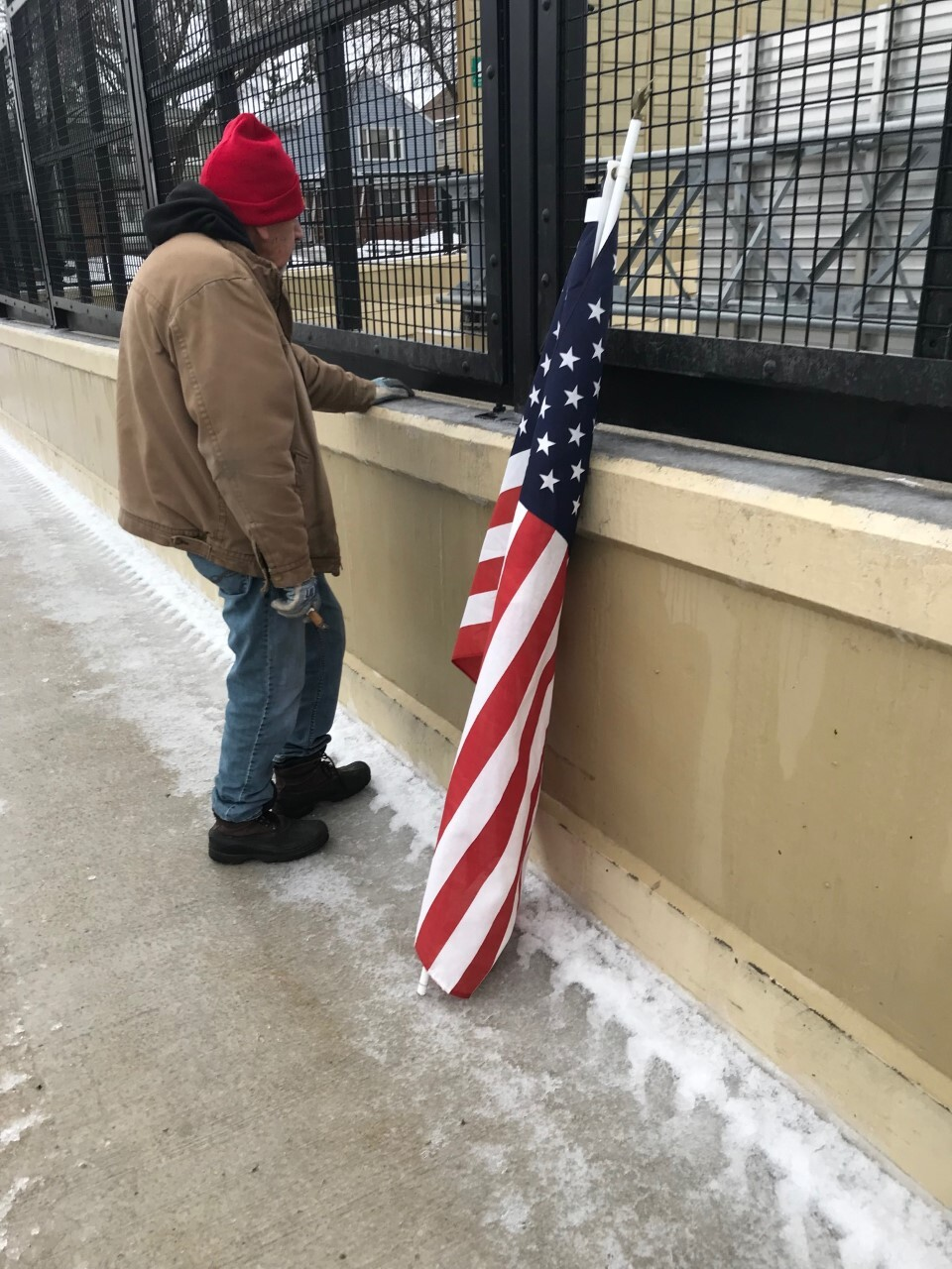 A man waits to honor the fallen officer before for the procession on 92nd Street.