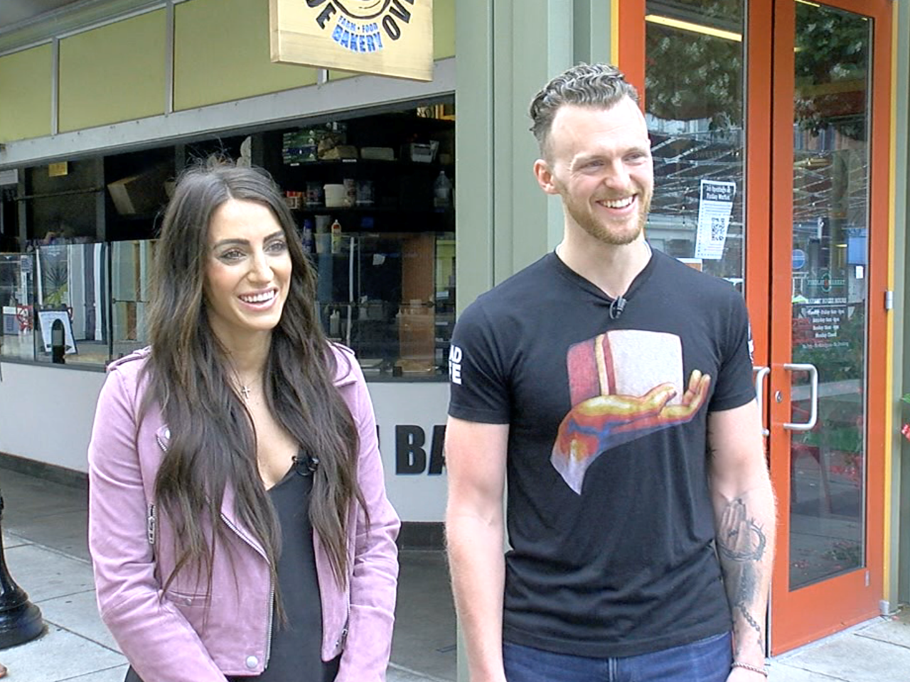 From left, Kristen and William Schumacher stand outside the Blue Oven Bakery location at Findlay Market. Kristen has long dark hair and is wearing a black top and pink jacket. William has short, brown hair and a beard and mustache. He is wearing a black t-shirt and jeans.