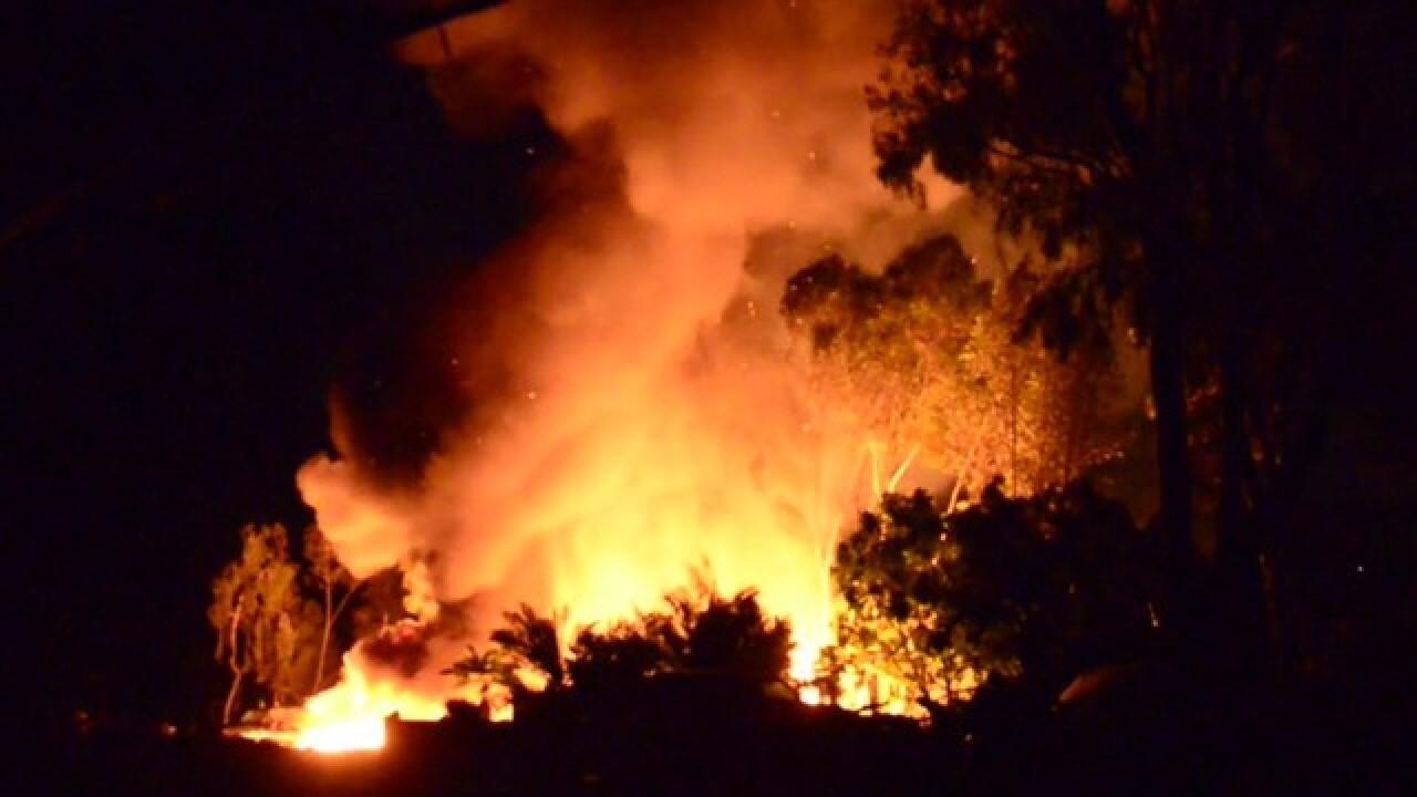 Brush fire engulfs cars, threatens homes