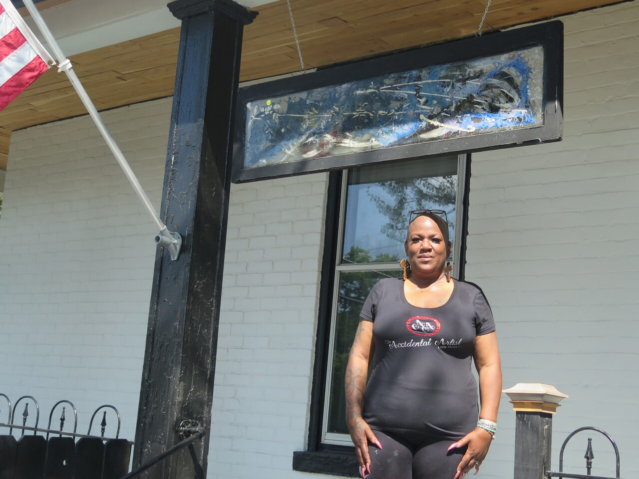 Nina Edwards standing on the front porch of the house where Annie Hargraves once lived. Above her is one of the old windows from the house that Edwards painted. Photo taken Aug. 24, 2021. The window has an abstract design that includes blue, black and white.