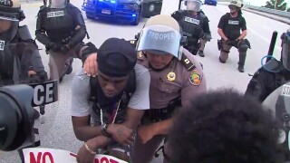 A Florida Highway Patrol trooper kneels in solidarity with a protester in Boca Raton, Fla., on June 1, 2020.