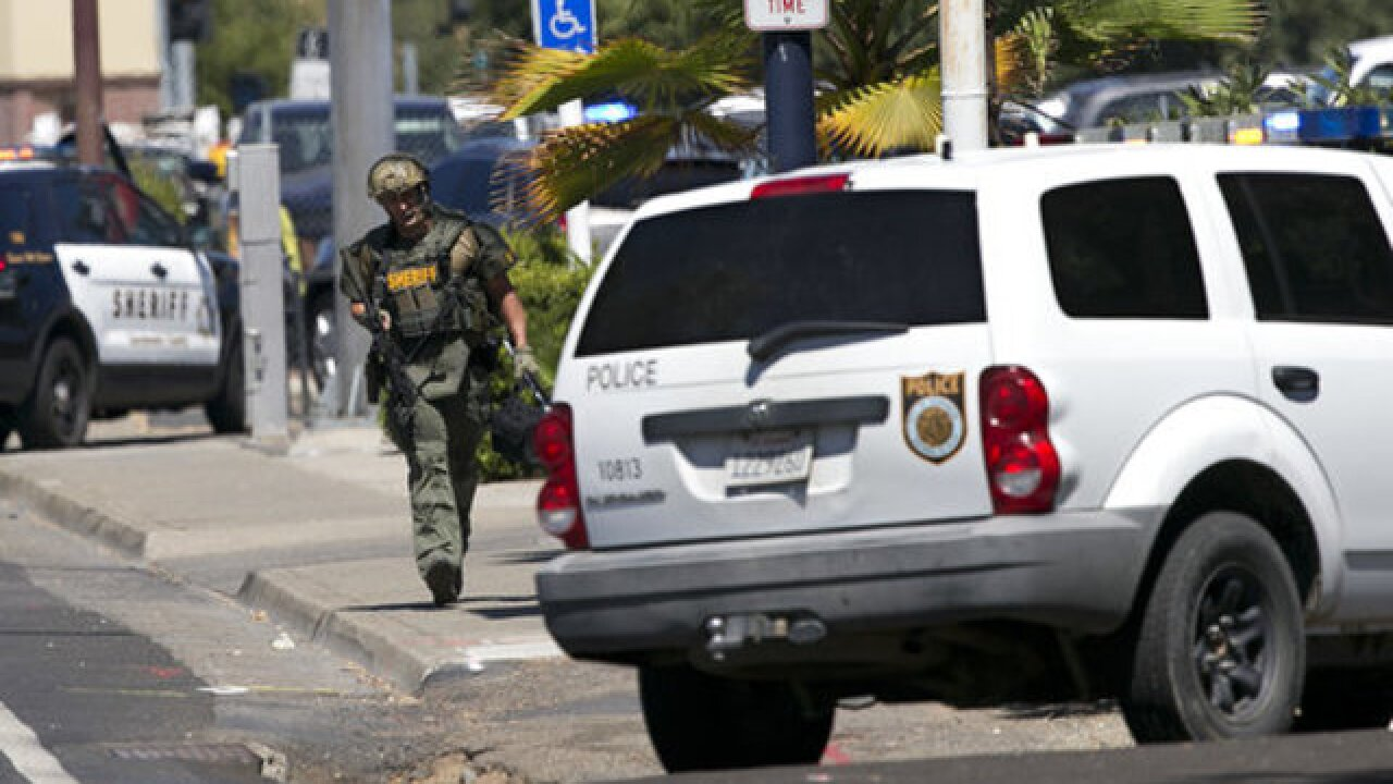 Authorities surround hotel after 3 officers shot