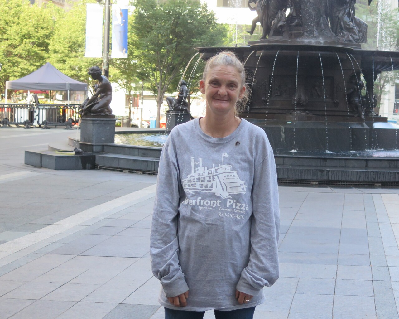 Mary Caldwell poses for a photo at Fountain Square on Aug. 5, 2021. She's wearing a long-sleeved gray t-shirt and has her long hair pulled back in a ponytail.