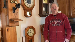 Charles Edwards, wearing a red Indiana Hoosiers zip-up hooded jacket, poses with some of the antique clocks and an antique phone in his collection.