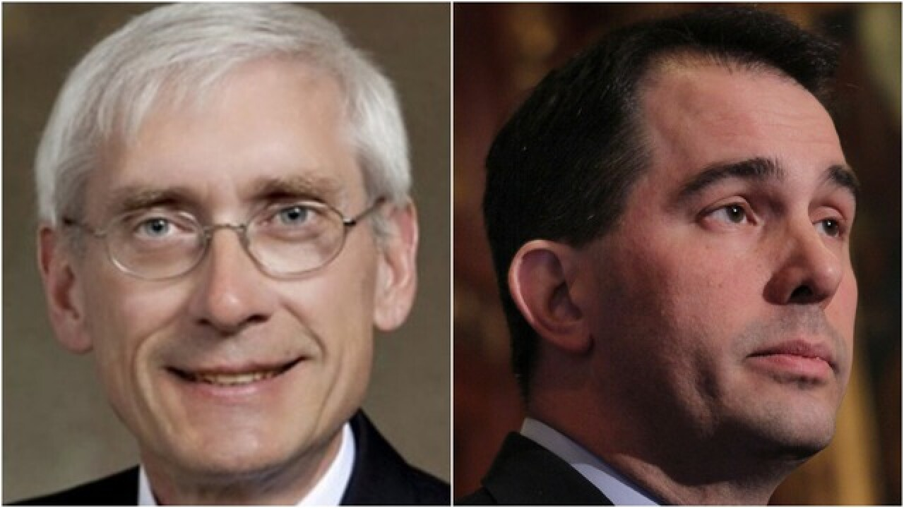 Walker, Evers spar over cost of health insurance