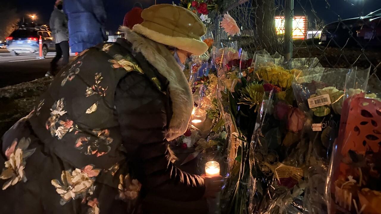 Woman lights candle at vigil in Boulder