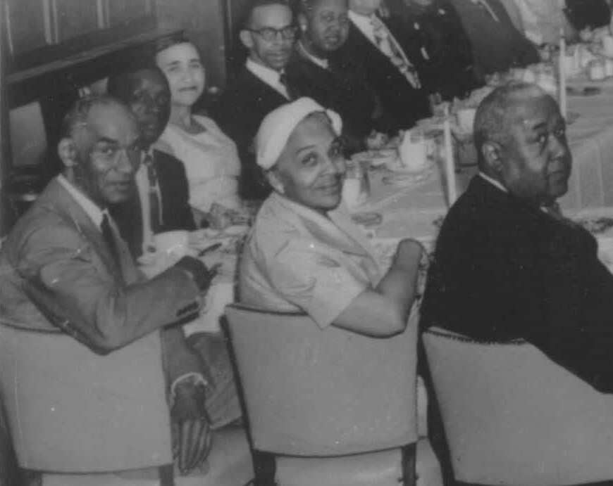 This photo from the Kenton County Public Library's collection shows Annie Hargraves at a Utopian Club meeting at the Manse Hotel in Cincinnati. Hargraves is third from the left, wearing a pale dress and no hat. The photo was taken around 1950.