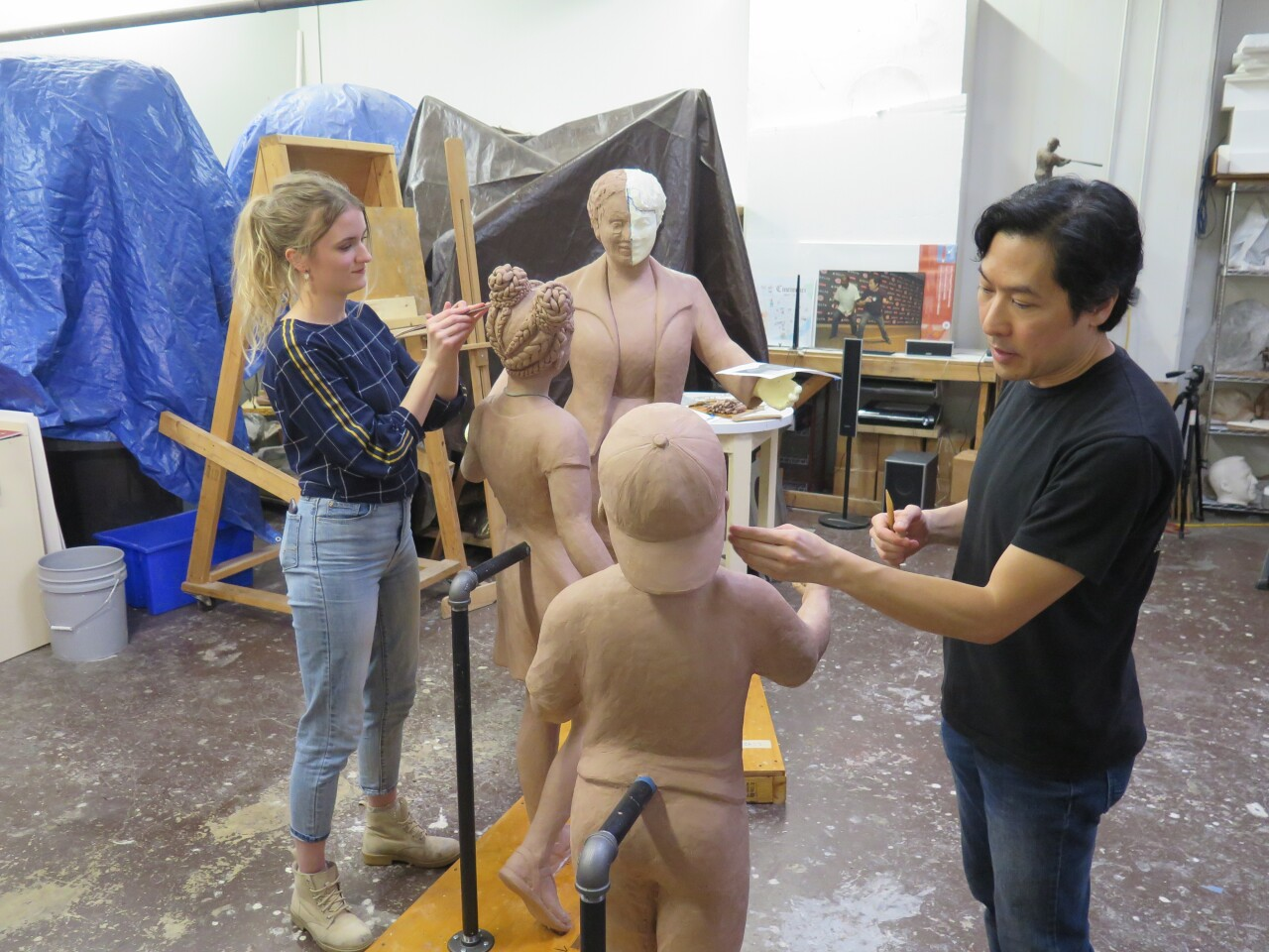 From left, Gina Erardi and Tom Tsuchiya work on full-size forms for a sculpture honoring civil rights icon Marian Spencer.