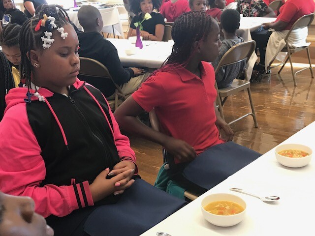 Students wait to eat their soup