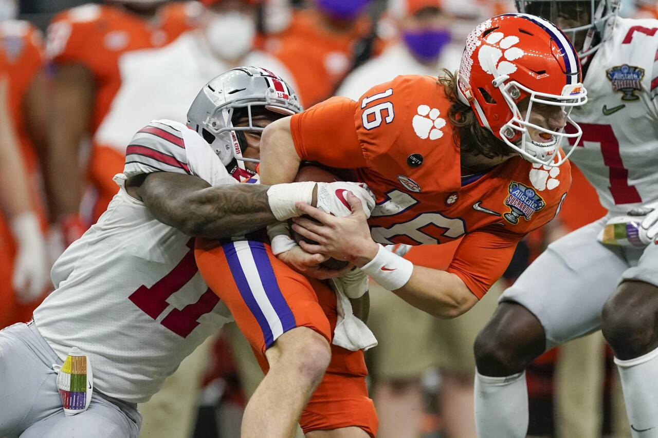 Clemson Tigers QB Trevor Lawrence tackled by Ohio State Buckeyes defensive end Tyreke Smith in College Football Playoff semifinal at Sugar Bowl