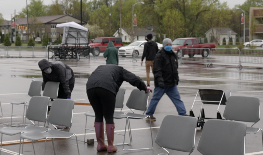 MSU staff measuring distance between chairs for graduation ceremony