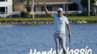 Matt Jones raises golf ball in air after winning 2021 Honda Classic