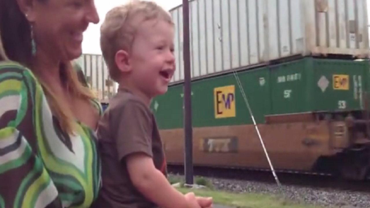 Toddler realizes his dad is driving passing train, reacts hilariously