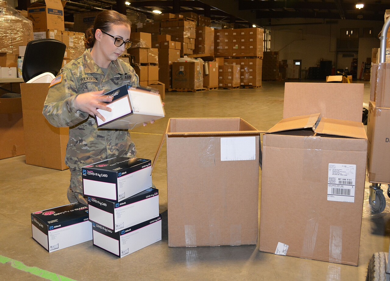 SPC Patricia Fulkerson preparing a box of rapid antigen tests kits for shipping at the state warehouse.