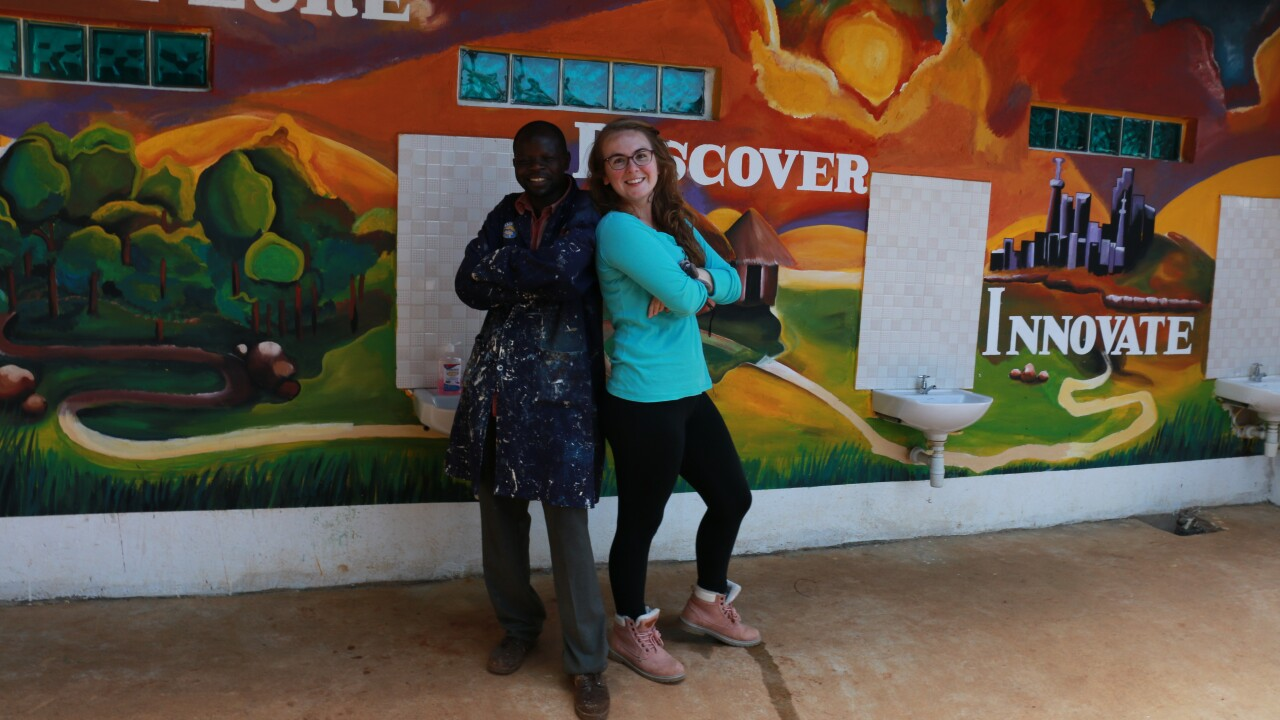 A man and a woman pose with their arms crossed and backs touching in front of a mural of the Western Kenyan landscape