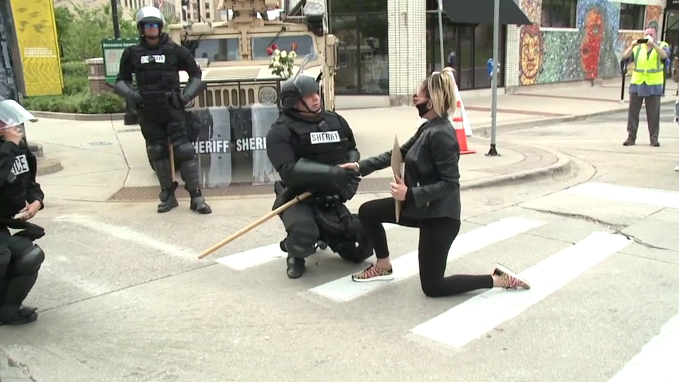 Protester and deputy kneeling