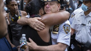 One of NYPD's top cops kneels, hugs protester