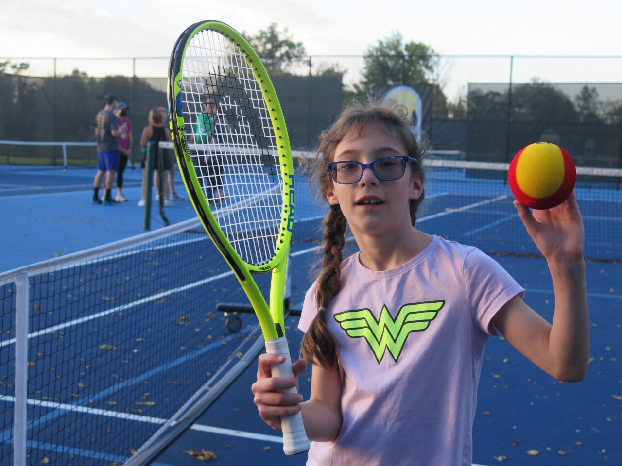Kaya Naser poses with a tennis racquet and ball on Oct. 11, 2021. Her long, dark hair is in braids, and she's wearing a pink Wonder Woman t-shirt.