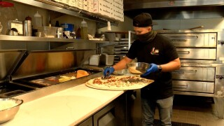 A worker prepares a pizza at Aunt Lulu's Pizza and Kitchen in Boca Raton on May 3, 2021.jpg