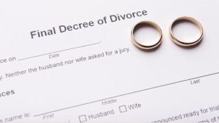 Two golden wedding rings on final divorce decree document