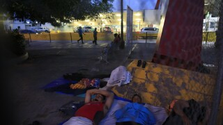 A small group of migrants waiting to seek asylum sleeps at the entrance to the Puerta Mexico international bridge in Matamoros, Tamaulipas state, Mexico, Friday, June 28, 2019. Hundreds of migrants from Central America, South America, the Caribbean and Africa have been waiting, most in rented rooms or a distant shelter, for their number to be called at the bridge in downtown Matamoros, to have the opportunity to request asylum in the U.S.(AP Photo/Rebecca Blackwell)
