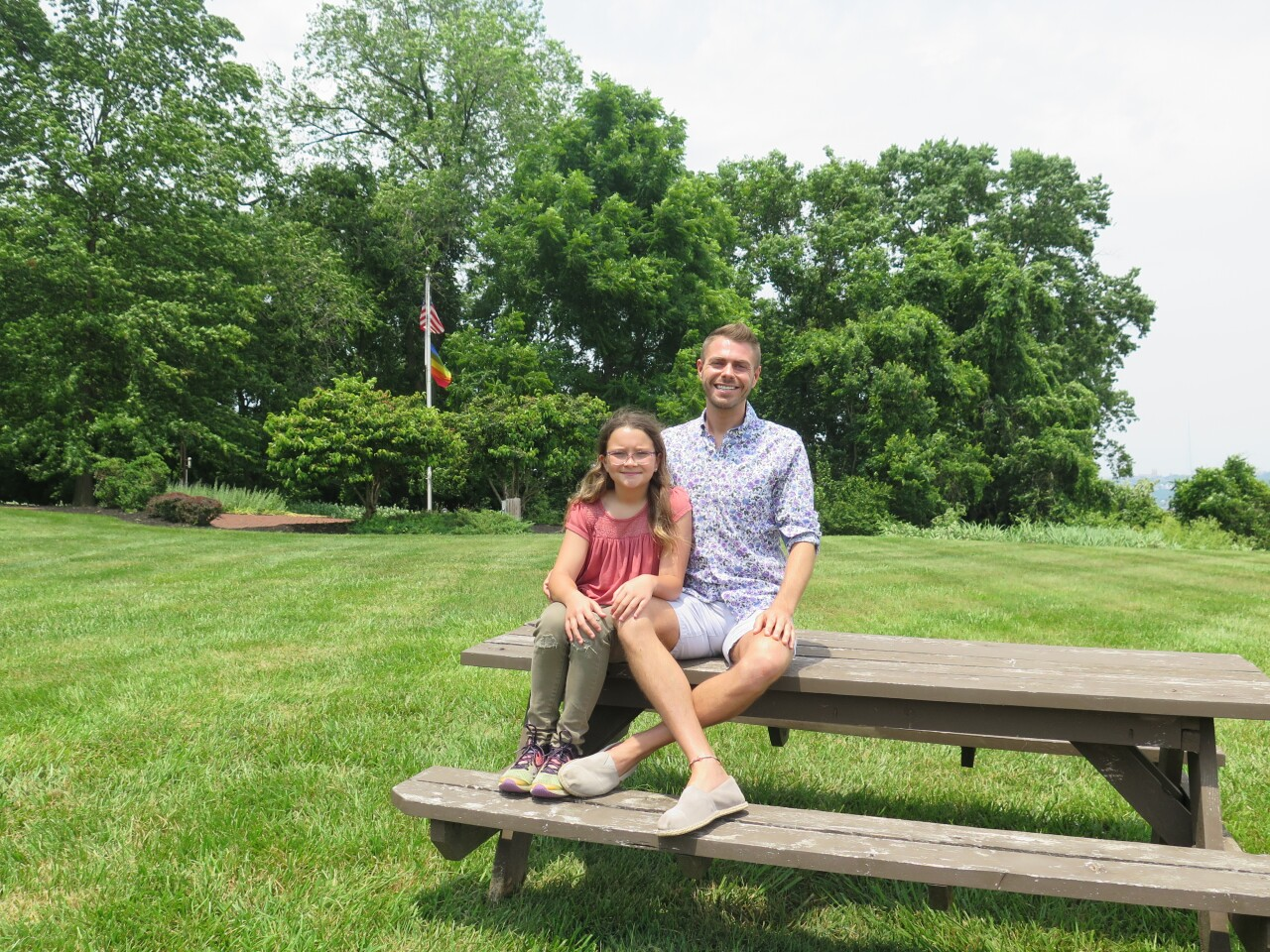 Harper Rae Allen, left, and her dad, Ryan Joseph Allen, pose for a portrait outside Children's Home of Northern Kentucky. Two flags - an American flag and a Pride flag - flutter on a flagpole behind them.