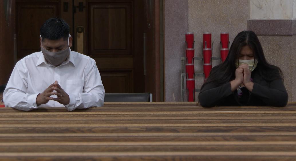 Vidal Ramirez and his wife praying at Holy Family church