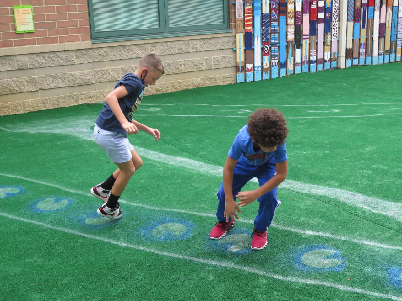 Dallas Meeker, left, and Kamdyn Crump hop across images of lily pads as part of the sensory path.
