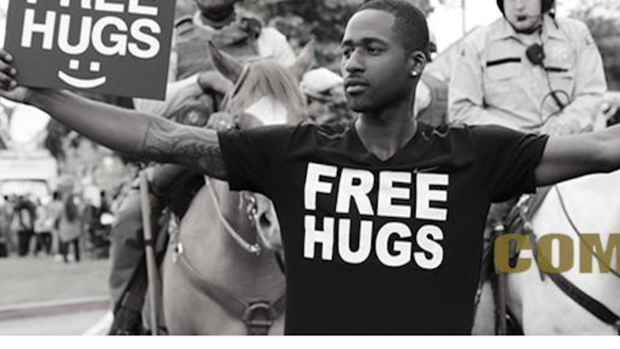 Man giving hugs to try to calm racial tensions