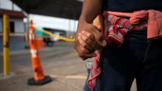 A Honduran migrant holds his daughter's hand at an immigration checkpoint in Nuevo Laredo..PNG