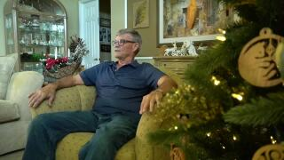 Jim Phelps sitting next to wooden Christmas ornaments