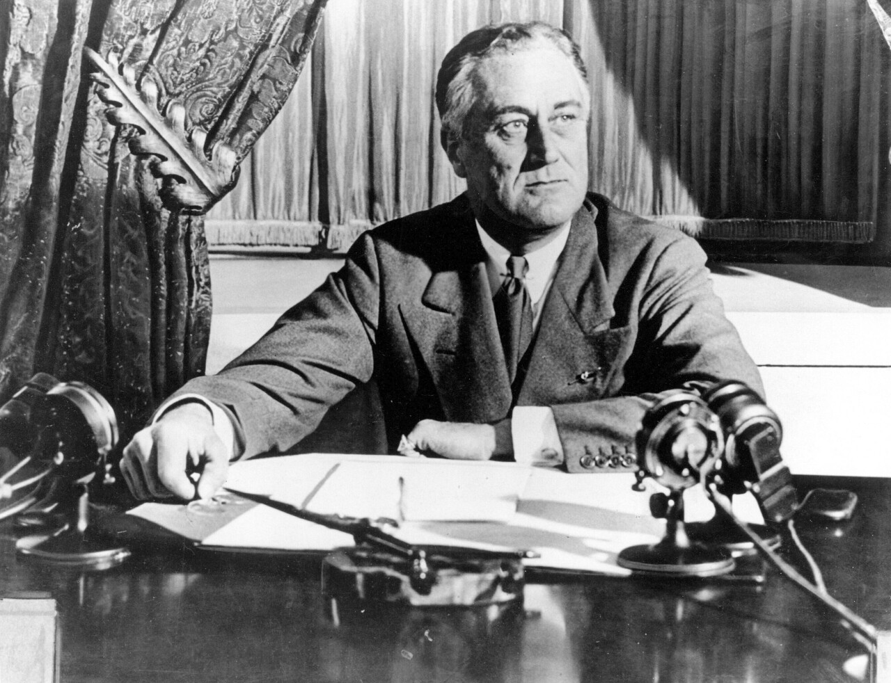 """In this March 1933, file photo, President Franklin D. Roosevelt delivers his first radio """"fireside chat"""" in Washington. The New Deal was a try-anything moment during the Great Depression that remade the role of the federal government in American life. (AP Photo)"""