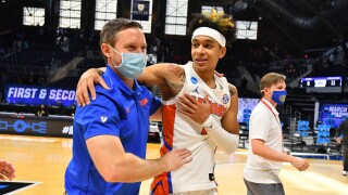 Florida Gators head coach Mike White and Tre Mann embrace after 2021 NCAA tournament win against Virginia Tech Hokies