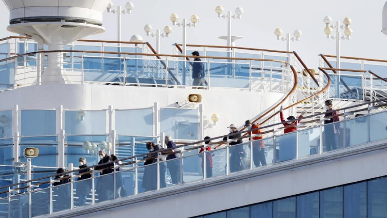 Passengers stand on the deck of the Diamond Princess cruise ship anchored at Yokohama Port in Yokohama, near Tokyo, Wednesday, Feb. 12, 2020. Japan's health ministry said Wednesday that 39 new cases of a virus have been confirmed on the cruise ship quarantined at the Japanese port. (Yuta Omori/Kyodo News via AP)