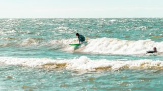 Cat Carrillo rides a wave on Lake Erie.