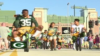 Packers players, kids ride bikes to practice