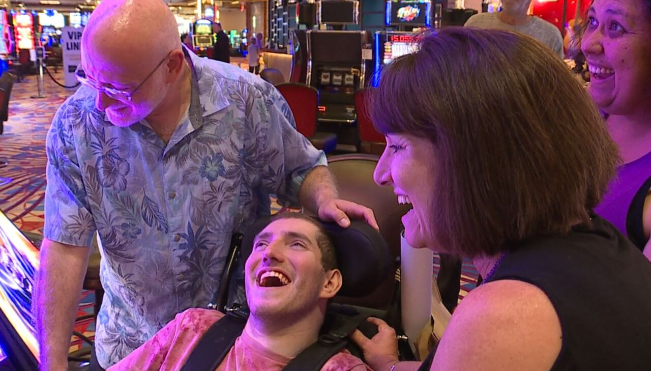 Ethan Kadish, center, smiles big after winning at slots at Hard Rock Casino Cincinnati. He's surrounded by his father, Scott Kadish, left, his mother, Alexia Kadish, right, and his nurse, Stephanie Johnstone-Wagner, behind him.