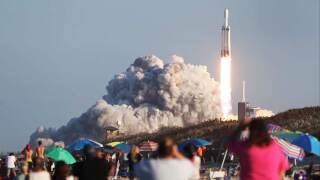 People watch as the SpaceX Falcon Heavy rocket lifts off from launch pad 39A at NASA's Kennedy Space Center on April 11, 2019 in Titusville, Florida. The rocket is carrying a communications satellite built by Lockheed Martin into orbit.