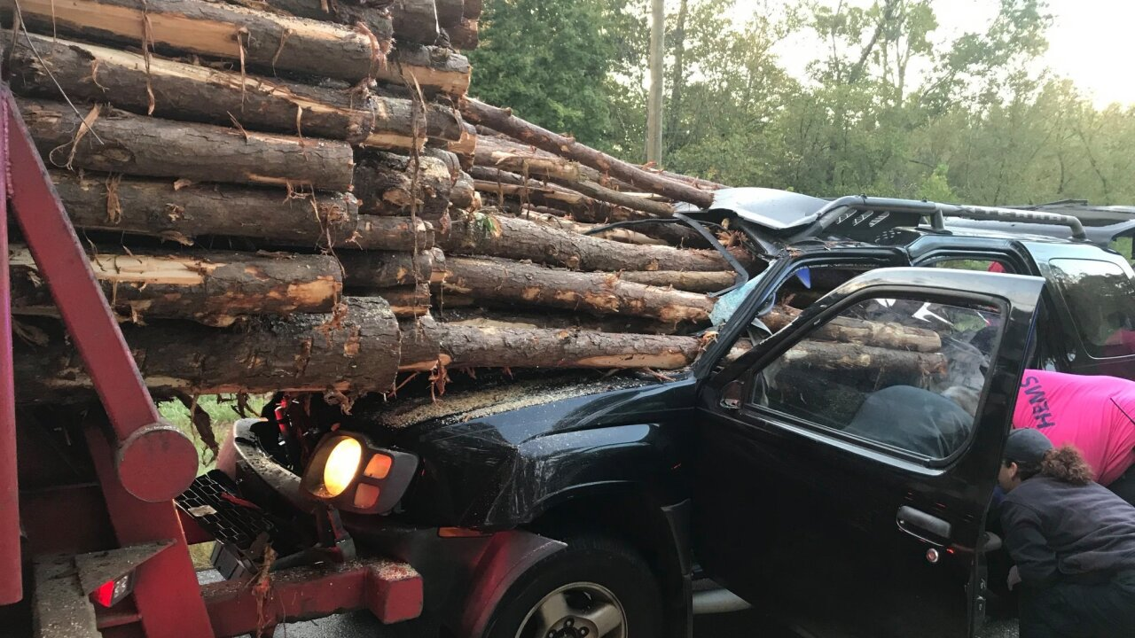 Driver survives after logs slide from truck, impale SUV